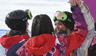 Jamie Anderson of the United States, right celebrates with Switzerland's Sina Candrian, center, and Britain's Jenny Jones, left, after Anderson won the women's snowboard slopestyle final at the 2014 Winter Olympics, Sunday, Feb. 9, 2014, in Krasnaya Polyana, Russia. (AP Photo/Sergei Grits)