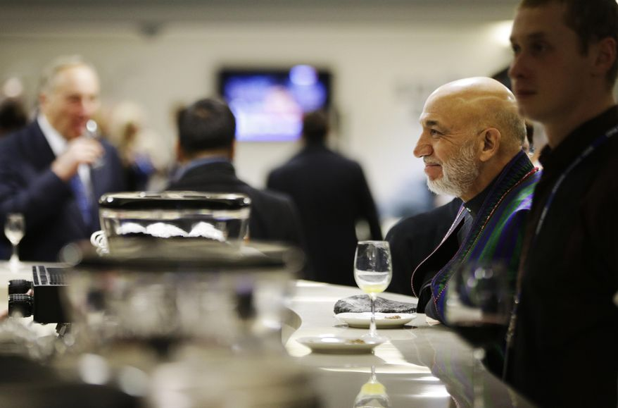 Afghan President Hamid Karzai, right, waits to order a coffee in the presidential lounge before the opening ceremony of the 2014 Winter Olympics, Friday, Feb. 7, 2014, in Sochi, Russia. (AP Photo/David Goldman, Pool)