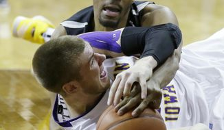 Wichita State forward Darius Carter, top, tries to steal the ball from Northern Iowa forward Seth Tuttle during the second half of an NCAA college basketball game on Saturday, Feb. 8, 2014, in Cedar Falls, Iowa. (AP Photo/Charlie Neibergall)