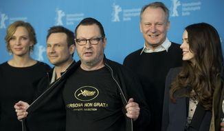 Director Lars von Trier, centre, reveals a tee shirt which has the Cannes film festival symbol and the slogan Persona Non Grata underneath as he poses for photographers at the photo call for the film Nymphomaniac at the International Film Festival Berlinale in Berlin, Sunday, Feb. 9, 2014. In 2011 Von Trier was asked to leave the Cannes film festival after a bizarre, rambling news conference in which he said he sympathizes with Adolf Hitler. (AP Photo/Axel Schmidt)