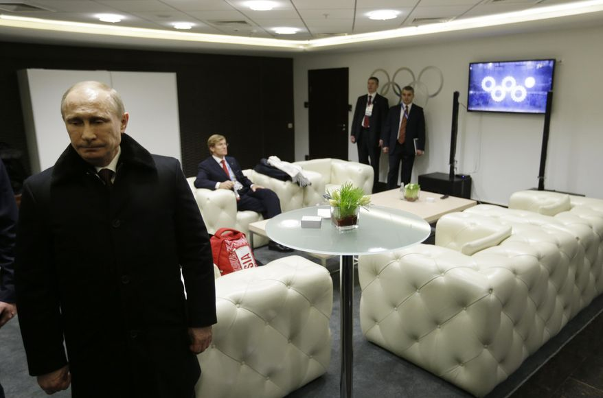 In this first in a sequence of four images, Russian President Vladimir Putin waits in the presidential lounge to be introduced at the opening ceremony of the 2014 Winter Olympics on Friday, Feb. 7, 2014, in Sochi, Russia. Behind him, a TV screen shows four of the Olympic rings opening at the start of the ceremony, while the fifth ring remains closed. (AP Photo/David Goldman, Pool)