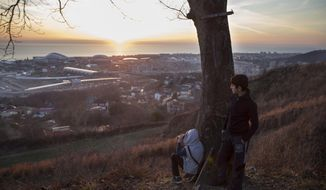 Caucasian boys look through binoculars from a hill overlooking Sochi Olympic Park before the opening ceremony of the 2014 Winter Olympics, as the sun sets over the Black Sea Friday, Feb. 7, 2014, in Sochi, Russia.  Part of the Olympic park in background with Fisht Olympic Stadium, top left, and Bolshoi Ice Dome, to right of Fisht. (AP Photo/Pavel Golovkin)