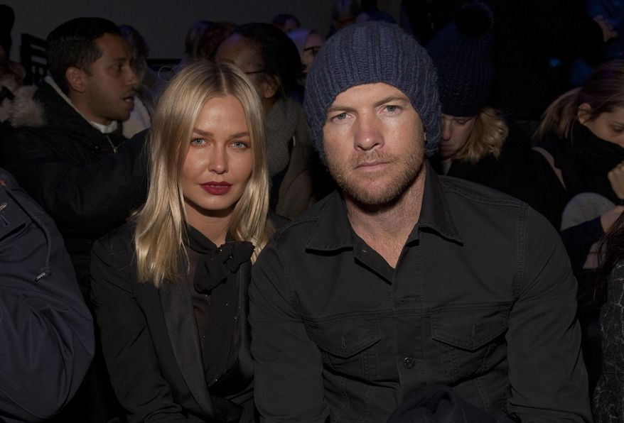 Fashion model Lara Bingle, left, and actor Sam Worthington, right, attend the MBFW 2014 Fall/Winter Alexander Wang fashion show, on Saturday, Feb. 8, 2014 in New York. (Photo by Andy Kropa/Invision/AP)