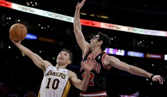 Los Angeles Lakers' Steve Nash, left, shoots over Chicago Bulls' Kirk Hinrich during the first half of an NBA basketball game in Los Angeles, Sunday, Feb. 9, 2014. (AP Photo/Chris Carlson)