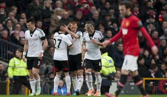 Fulham's Steve Sidwell, centre, celebrates with teammates after scoring against Manchester United during their English Premier League soccer match at Old Trafford Stadium, Manchester, England, Sunday Feb. 9, 2014. (AP Photo/Jon Super)