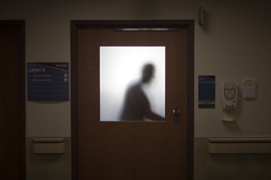 In this Friday, Jan. 24, 2014, file photo, a doctor is silhouetted against a glass window while opening a door to leave an exam room after visiting a patient at Grady Memorial Hospital, in Atlanta. (AP Photo/David Goldman) ** FILE *