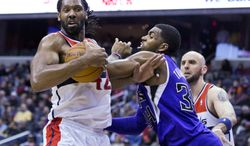Washington Wizards power forward Nene, left, fights Sacramento Kings power forward Jason Thompson for a rebound during the second half of an NBA basketball game, Sunday, Feb. 9, 2014, in Washington. The Wizards defeated the Kings 93-84. (AP Photo/ Evan Vucci)