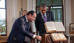 From a different angle: President Obama and French President Francois Hollande examine items on the desk of Thomas Jefferson on Monday. The visit to Monticello by the liberal and socialist leaders carried ironic and contradictory overtones. (Associated Press)