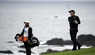 Jimmy Walker, right, follows through on his shot on the ninth fairway Sunday, Feb. 9, 2014, during the final round of the AT&T Pebble Beach Pro-Am golf tournament in Pebble Beach, Calif.  (AP Photo/Ben Margot)