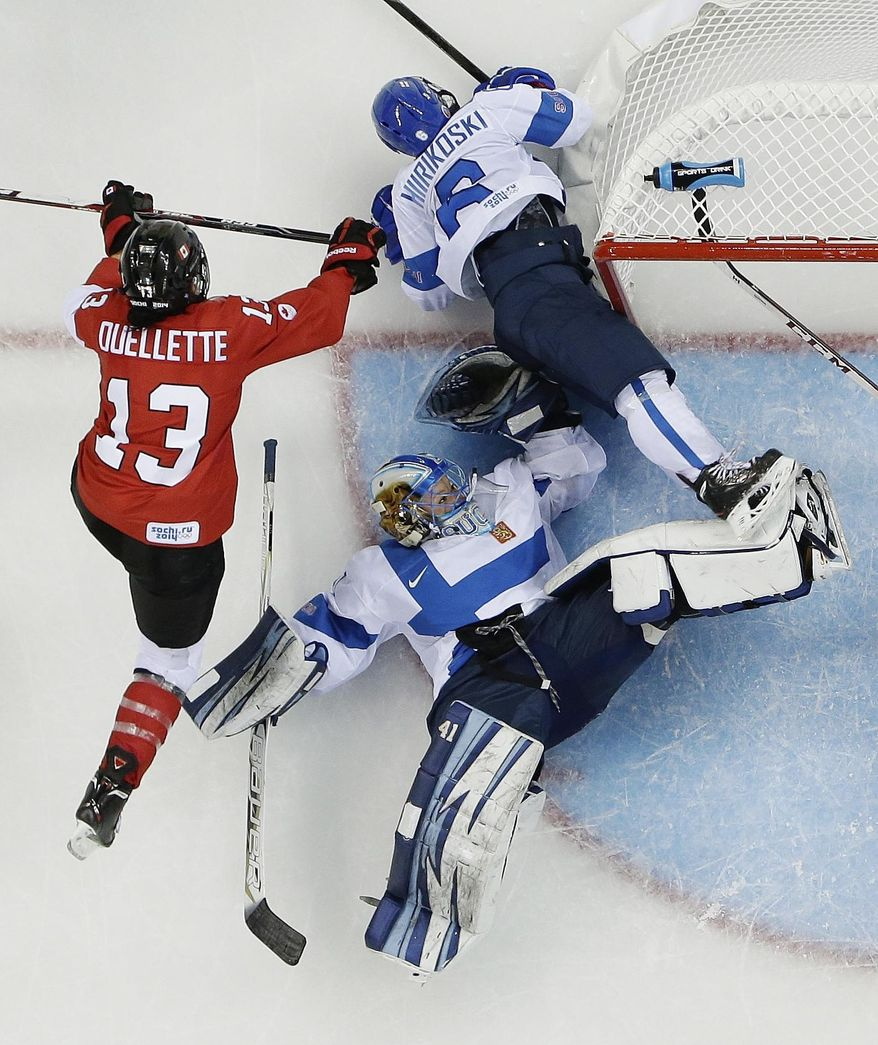 Goalkeeper Noora Raty lands on her back as she and Jenni Hiirikoski (6) of Finland defend the goal under pressure form Caroline Ouellette (13) of Canada during the 2014 Winter Olympics women's ice hockey game at Shayba Arena, Monday, Feb. 10, 2014, in Sochi, Russia. Canada defeated Finland 3-0. (AP Photo/Matt Slocum)