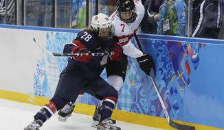 Amanda Kessel of the Untied States traps Lara Stalder of Switzerland up against the boards during the 2014 Winter Olympics women's ice hockey game at Shayba Arena, Monday, Feb. 10, 2014, in Sochi, Russia. USA defeated Switzerland 9-0. (AP Photo/Matt Slocum)
