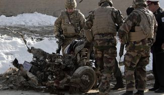 U.S. soldiers search the site where a suicide attacker rammed a car bomb into a NATO convoy killing two foreign civilian contractors, in the Afghan capital Kabul, Afghanistan, Monday, Feb. 10, 2014. The Islamic militant group Hizb-i-Islami claimed responsibility for the attack in eastern Kabul, saying it would drive all foreign forces from Afghanistan. (AP Photo/Rahmat Gul)