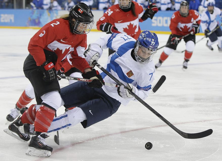 Susanna Tapani of Finland falls as she challenges Meghan Agosta-Marciano of Canada for control of the puck during the third period of the 2014 Winter Olympics women's ice hockey game at Shayba Arena, Monday, Feb. 10, 2014, in Sochi, Russia. (AP Photo/Matt Slocum)