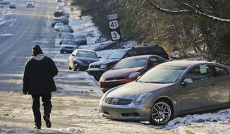 FILE - In this Thursday, Jan. 30, 2014, file photo, cars abandoned during an earlier snowstorm sit idle along Northside Parkway in Atlanta. With memories of thousands of vehicles gridlocked for hours on icy metro Atlanta highways fresh in their minds, emergency officials and elected leaders in north Georgia were preparing Monday, Feb. 10, 2014, for another round of winter weather. (AP Photo/Atlanta Journal & Constitution, John Spink, File)