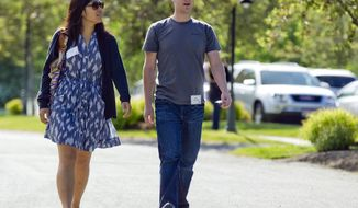 ** FILE ** In this July 9, 2011, file photo, Mark Zuckerberg, president and CEO of Facebook, walks with Priscilla Chan during the 2011 Allen and Co. Sun Valley Conference, in Sun Valley, Idaho. Zuckerberg and his wife, Chan, were the most generous American philanthropists in 2013, The Chronicle of Philanthropy reported, Monday, Feb. 10, 2014, with a donation of 18 million Facebook shares, valued at more than $970 million, given to a Silicon Valley nonprofit in December. (AP Photo/Julie Jacobson, File)