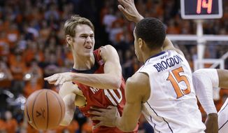 Maryland forward Jake Layman (10) looks to pass as Virginia guard Malcolm Brogdon (15) defends during the first half of an NCAA college basketball game in Charlottesville, Va., Monday, Feb. 10, 2014. (AP Photo/Steve Helber)