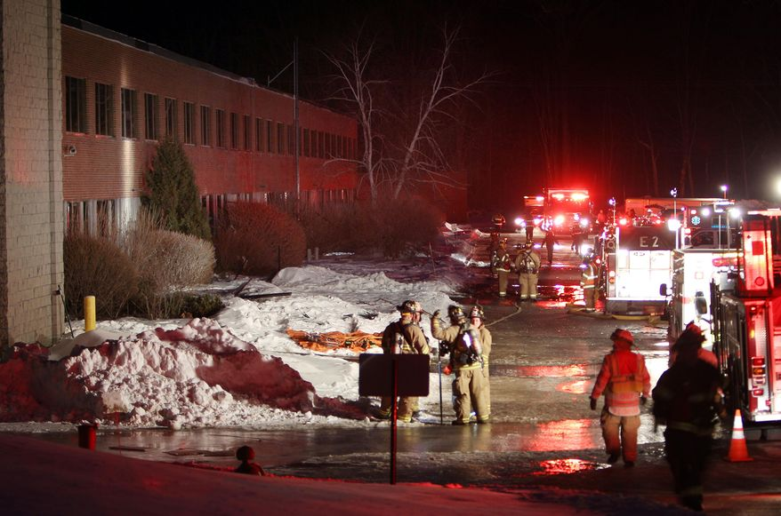 Emergency crews from several towns work an area outside the New Hampshire Ball Bearing plant after an explosion, Monday, Feb. 10, 2014 in Peterborough, N.H. At least 13 people were injured, but a company spokeswoman says none of the injuries appears to be life-threatening. (AP Photo/Jim Cole)