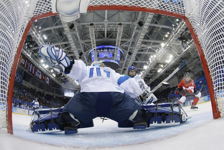 Rebecca Johnston's of Canada shot sails past Goalkeeper Noora Raty of Finland for a goal during the third period of the 2014 Winter Olympics women's ice hockey game at Shayba Arena, Monday, Feb. 10, 2014, in Sochi, Russia. Canada defeated Finland 3-0. (AP Photo/Matt Slocum, Pool)