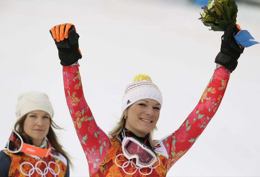 Women's supercombined gold medal winner Germany's Maria Hoefl-Riesch and bronze medal winner United States' Julia Mancuso celebrate after a flower ceremony at the Sochi 2014 Winter Olympics, Monday, Feb. 10, 2014, in Krasnaya Polyana, Russia. (AP Photo/Charles Krupa)