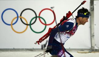 Norway's Ole Einar Bjoerndalen skis past the Olympic rings during the men's biathlon 12.5k pursuit, at the 2014 Winter Olympics, Monday, Feb. 10, 2014, in Krasnaya Polyana, Russia. (AP Photo/Lee Jin-man)