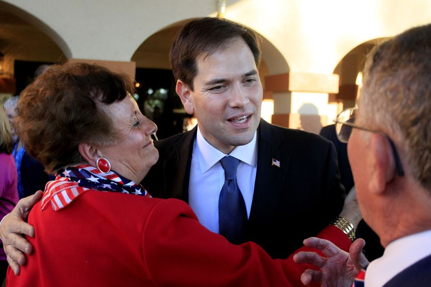 U.S. Sen. Marco Rubio gets hugs from Judith Jolly, left, David Jolly's mom, while greeting she and Lawson Jolly, Jr., right, David Jolly's dad, while Rubio and Republican congressional candidate David Jolly meet with residents and the media as they visit the Lake Seminole Square retirement center in Seminole Monday, Feb. 10, 2014. (AP Photo/The Tampa Bay Times, Dirk Shadd )