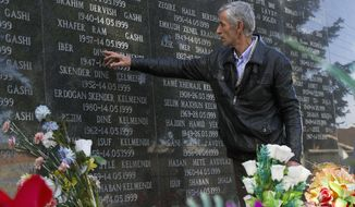 """Rexhe Kelmendi, one of three survivors of the Cuska massacre, points out the names of family members as he visits the Martyr's cemetery in the village of Cuska, Kosovo on Tuesday, Feb. 11, 2014. Serbia's war crimes court on Tuesday convicted nine former paramilitaries of the brutal killings of more than 100 ethnic Albanian civilians during the Kosovo war and sentenced them to between two and 20 years in prison. The crime by the """"Jackals"""" paramilitary group includes the massacre of 41 people in the Kosovo village of Cuska where Serbs rounded up villagers, robbed them, separated women and children from men, locked the men in a house and set it on fire. The brutality of Serbia's crackdown prompted NATO to intervene with airstrikes to stop the war. (AP Photo/Visar Kryeziu)"""