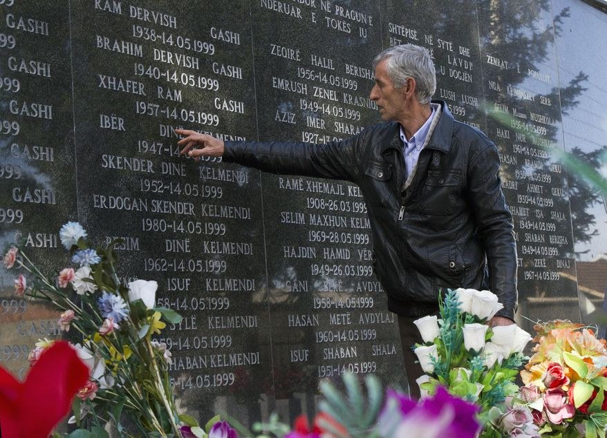 "Rexhe Kelmendi, one of three survivors of the Cuska massacre, points out the names of family members as he visits the Martyr's cemetery in the village of Cuska, Kosovo on Tuesday, Feb. 11, 2014. Serbia's war crimes court on Tuesday convicted nine former paramilitaries of the brutal killings of more than 100 ethnic Albanian civilians during the Kosovo war and sentenced them to between two and 20 years in prison. The crime by the ""Jackals"" paramilitary group includes the massacre of 41 people in the Kosovo village of Cuska where Serbs rounded up villagers, robbed them, separated women and children from men, locked the men in a house and set it on fire. The brutality of Serbia's crackdown prompted NATO to intervene with airstrikes to stop the war. (AP Photo/Visar Kryeziu)"
