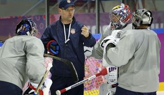 USA head coach Dan Bylsma, center, talks to his three goalies during a training session at the Bolshoy Ice Dome at the the 2014 Winter Olympics, Tuesday, Feb. 11, 2014, in Sochi, Russia. (AP Photo/Julio Cortez)