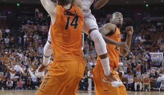 Texas' Isaiah Taylor (1) crashes into Oklahoma State's Marek Soucek (14) as he drives to the basket during the first half on an NCAA college basketball game, Tuesday, Feb. 11, 2014, in Austin, Texas. (AP Photo/Eric Gay)
