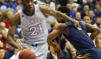 Kansas center Joel Embiid (21) pushes off West Virginia forward Devin Williams, right, during the first half of an NCAA college basketball game in Lawrence, Kan., Saturday, Feb. 8, 2014. Embiid scored 11 points in the game. Kansas defeated West Virginia 83-69. (AP Photo/Orlin Wagner)