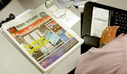 A copy of the Mundo Hispanico newspaper with a headline on the Arizona immigration law sits next to reporter Mario Guevara as he works in the newsroom Thursday, July 5, 2012, in Norcross, Ga. The reporter for Georgia's largest Spanish-language newspaper who frequently writes about immigration issues has recently found himself caught up in his own immigration drama. (AP Photo/David Goldman)