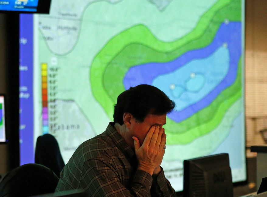 A weary Chuck Ray, director of field operations for the Georgia Emergency Management Agency, rubs his eyes as he works in the emergency-operations center in Atlanta on Tuesday, as Georgia braces for a winter storm. Accumulation in the D.C. area will depend on whether or when the snow changes over to sleet or rain. (associated press)
