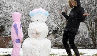 Jordan Larson-Horstman and her daughter Jane, 4, build a snowman on Queens Rd. Tuesday Feb. 11, 2104 in Charlotte, N.C. Most of North Carolina's southern tier was already covered in snow Tuesday in advance of a winter storm that forecasters predict will bring even more snow and a significant accumulation of ice in some areas. (AP Photo/The Charlotte Observer, Diedra Laird) MAGS OUT; TV OUT; NEWSPAPER INTERNET ONLY