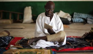 Marabou Husein Aba Ali reads prayers at the mosque at PK12, the last checkpoint at the exit of the town, Tuesday Feb. 11, 2014, where he and 3500 other Muslims have sought refuge from sectarian violence, awaiting for transport from Bangui, Central African Republic, to neighboring Chad. (AP Photo/Jerome Delay)