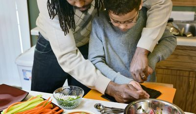 ADVANCE FOR USE MONDAY, FEB. 17 AND THEREAFTER - In this photo taken on Feb. 1, 2014, Desi Hall helps his son, Isaiah, 11, with the difficult task of cutting the seaweed before Isaiah made his own California roll sushi in St. Cloud, Minn. Isaiah has cooked for eight years. He writes the blog and has a YouTube channel featuring his cooking videos. (AP Photo/St. Cloud Times, Kimm Anderson) NO SALES