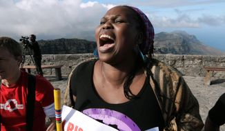 "This undated photo provided by the Sundance Institute shows a scene from the short film, ""One Billion Rising,"" of a woman rising on Table Mountain in Capetown, South Africa. The film was co-directed by Eve Ensler and Tony Stroebel.  ""One Billion Rising"" premiered at the Sundance Film Festival last month and is now free to watch online - just in time to for this year's event on Friday, Feb. 14, 2014. (AP Photo/Sundance Institute, Jasyn Howes)"