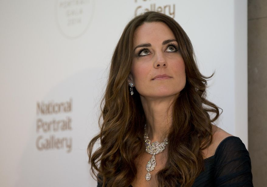 Kate Duchess of Cambridge waits to make a few remarks at  a fund raising gala at the National Portrait Gallery in London, Tuesday, Feb. 11, 2014. . The Duchess is wearing a dress by British designer Jenny Packham and a necklace on loan from Queen Elizabeth II that was given to the Queen as a gift for her wedding in 1947. (AP Photo/Alastair Grant, Pool)