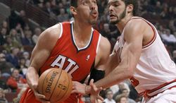 Atlanta Hawks forward Gustavo Ayon (14) looks to the basket as Chicago Bulls center Joakim Noah (13) defends during the first half of an NBA basketball game Tuesday, Feb. 11, 2014, in Chicago. (AP Photo/Charles Rex Arbogast)