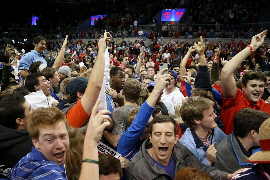 An SMU player gets caught in the melee after fans stormed the court following an NCAA college basketball game Saturday, Feb. 8, 2014, in Dallas. SMU defeated Cincinnati 76-55. (AP Photo/The Dallas Morning News, Brad Loper) MANDATORY CREDIT; MAGS OUT; TV OUT; INTERNET USE BY AP MEMBERS ONLY; NO SALES
