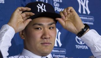 New York Yankees' pitcher Masahiro Tanaka puts on his baseball cap as he is introduced to the media at Yankee Stadium in New York Tuesday, Feb. 11, 2014. (AP Photo/Craig Ruttle)