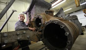 ADVANCE FOR MONDAY FEB. 17 - In this Feb. 5, 2014 photo, Steve Roudebush looks over the main cylinder of the C&NW 1385 locomotive at his shop, SPEC Machine, in Middleton, Wis. Steve Roudebush and Bruce Grill are craftsman, only metal is their specialty, not wood. For their latest repair project, the longtime friends and business partners at SPEC Machine are restoring a 107-year-old steam locomotive from the Mid-Continent Railway Museum in North Freedom. (AP Photo/Wisconsin State Journal, Amber Arnold)