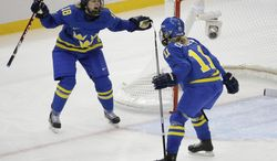Cecilia Ostberg of Sweden (11) celebrates her goal against Germany with teammate Anna Borgqvist (18) during the third period of the 2014 Winter Olympics women's ice hockey game at Shayba Arena, Tuesday, Feb. 11, 2014, in Sochi, Russia. (AP Photo/Mark Humphrey)