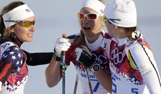 Norway's Astrid Uhrenholdt Jacobsen, center, is comforted by United States' Sophie Caldwell, left, and Sweden's Ida Ingemarsdotter, right, after the women's final of the cross-country sprint at the 2014 Winter Olympics, Tuesday, Feb. 11, 2014, in Krasnaya Polyana, Russia. (AP Photo/Matthias Schrader)