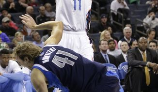 Dallas Mavericks' Dirk Nowitzki (41) falls after being injured guarding Charlotte Bobcats' Josh McRoberts (11) during the first half of an NBA basketball game in Charlotte, N.C., Tuesday, Feb. 11, 2014. Nowitzki was taken to the locker room after the play. (AP Photo/Chuck Burton)