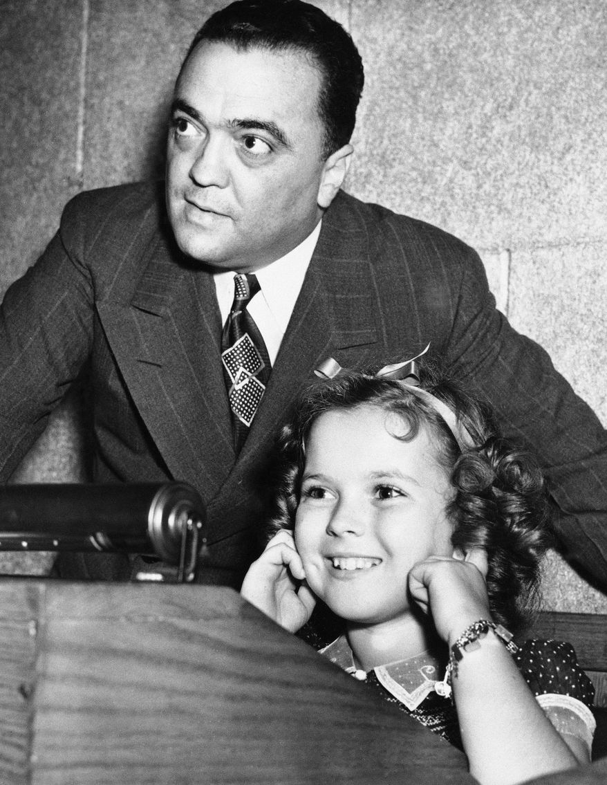 In this June 24, 1938, file photo, young actress Shirley Temple plugs her ears as her father shoots a federal agent's gun, while Federal Bureau of Investigation Director J. Edgar Hoover gives her a tour of FBI headquarters in Washington. Temple, who died at her home near San Francisco, Monday, Feb. 10, 2014, at 85, sang, danced, sobbed and grinned her way into the hearts of Depression-era moviegoers and remains the ultimate child star decades later. (AP Photo/File)