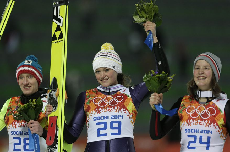 Germany's gold medal winner Carina Vogt is flanked by Austria's silver medal winner Daniela Iraschko-Stolz, left, and France's bronze medal winner Coline Mattel after the flower ceremony of the women's normal hill ski jumping final at the 2014 Winter Olympics, Tuesday, Feb. 11, 2014, in Krasnaya Polyana, Russia.(AP Photo/Matthias Schrader)