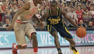 Michigan's Caris LeVert, right, drives the lane as Ohio State's Sam Thompson defends during the first half of an NCAA college basketball game, Tuesday, Feb. 11, 2014, in Columbus, Ohio. (AP Photo/Jay LaPrete)