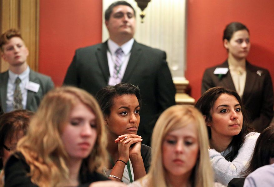 State Legislature interns Mahtub Zare Mochanloo, far right, and Sophanite Gedion, second row center, listen to testimony during a hearing on a bill which would allow Colorado public school teachers to carry concealed firearms during class, at the Capitol, in Denver, Tuesday, Feb. 11, 2014. The Republican proposal has been made before without success, but the suggestion has additional relevance after last year's Arapahoe High School shootings, in which a student targeted a teacher. (AP Photo/Brennan Linsley)