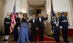 First Lady Michelle Obama and President Barack Obama with French President Francois Hollande, center, pose at the Grand Staircase as they arrive for a State Dinner at the White House in Washington, Tuesday, Feb. 11, 2014. (AP Photo/Pablo Martinez Monsivais)