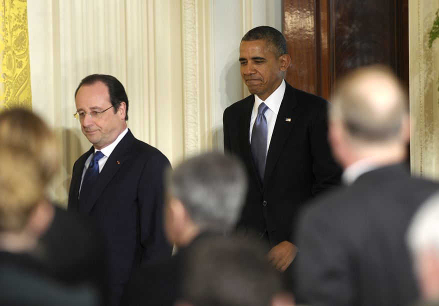 President Barack Obama follows French President Francois Hollande as they arrive for a joint news conference, as part of an official state visit, Tuesday, Feb. 11, 2014, in the East Room of the White House in Washington. (AP Photo/ Susan Walsh)